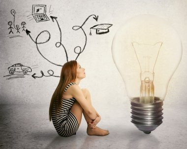 woman sitting in front of light bulb thinking has many thoughts life ideas
