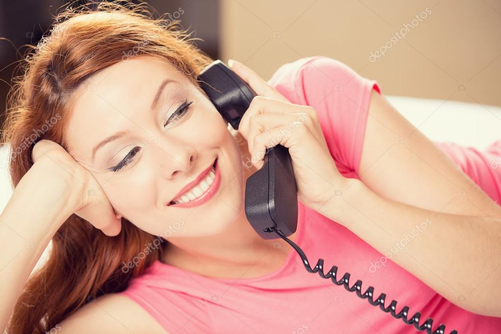 Happy woman talking on a phone lying in bed