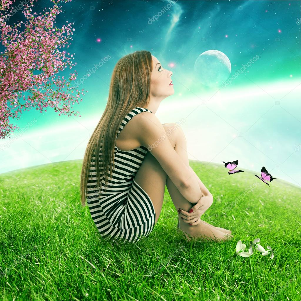 woman sitting on on a green meadow earth planet looking up at starry sky