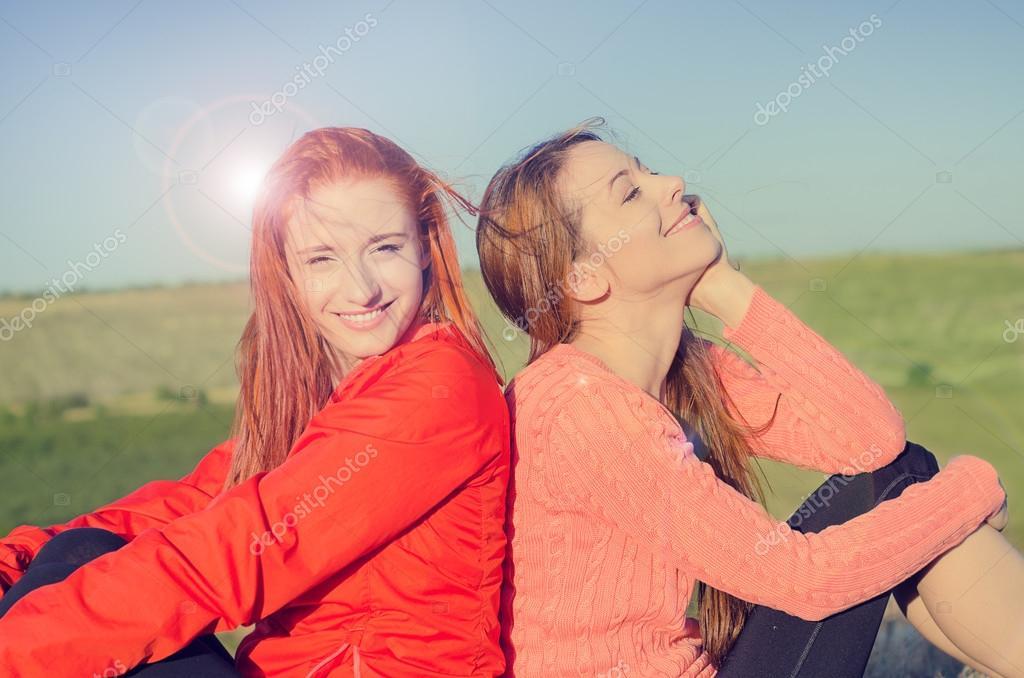 Two women smiling enjoying sunny weather blue sky nature celebrating freedom