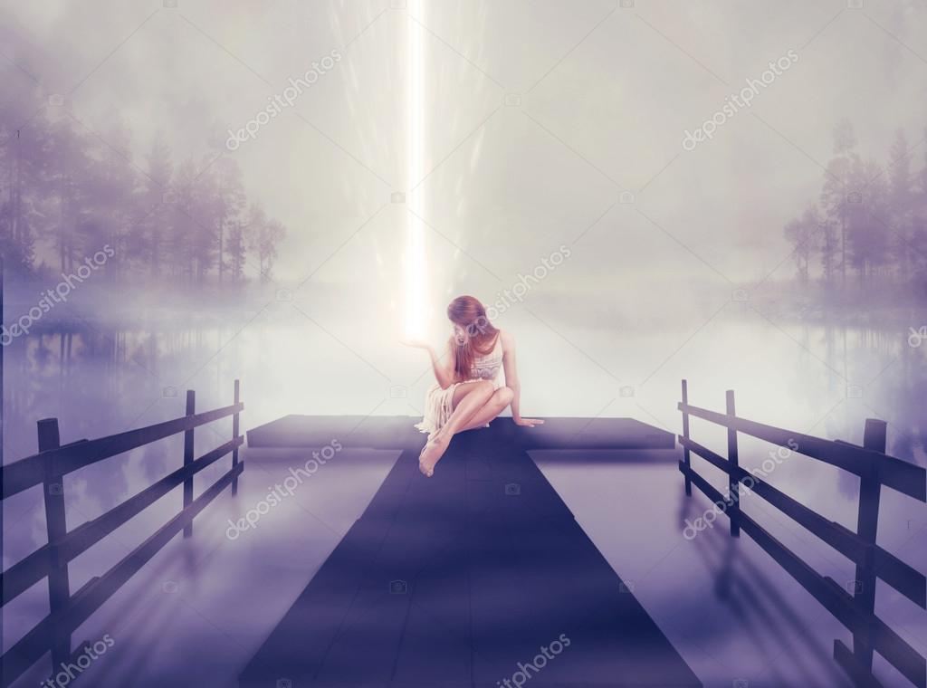 Lonely woman sitting on pier with ball of glowing light in her hand