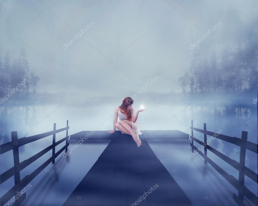 woman sitting on a lake pier with bright ball of glowing light in her hand