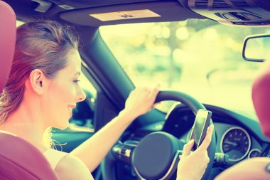 businesswoman sending text message using mobile phone while driving car