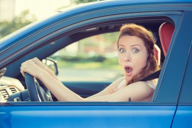 Distracted fright face of woman driving car