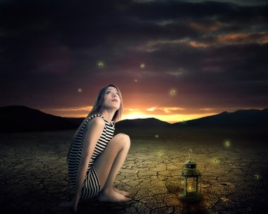 Lonely woman sitting in a middle of desert looking up on night skyline stars