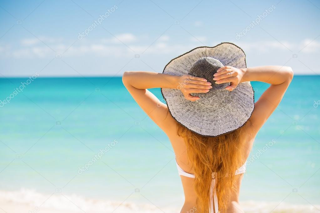 Woman enjoying beach relaxing joyful in summer by tropical blue water