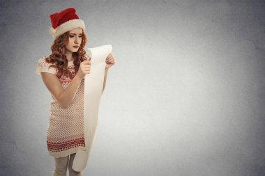 Christmas woman with red Santa Claus hat holding long wish list stressed out