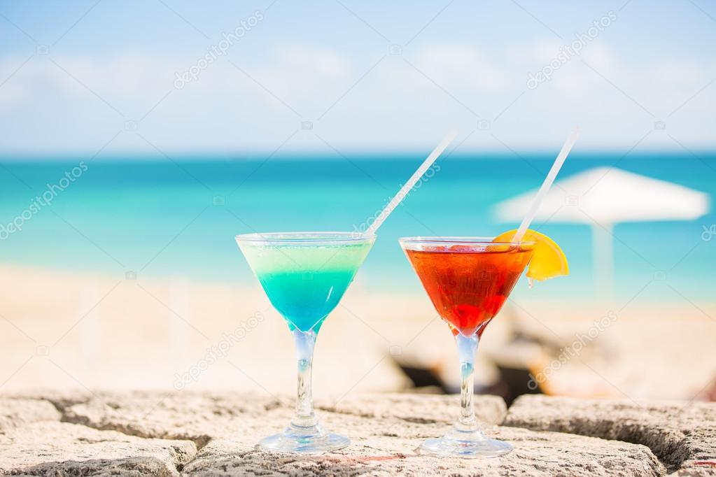 Two tropical cocktails on tropical beach ocean white sand and seascape