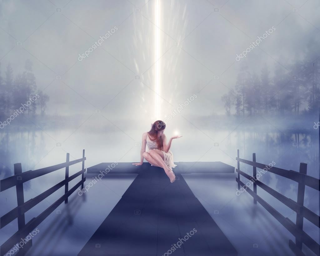 Lonely woman sitting on pier with bright ball of glowing light in her hand