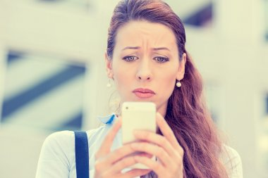 Upset stressed woman holding cellphone disgusted with message she received