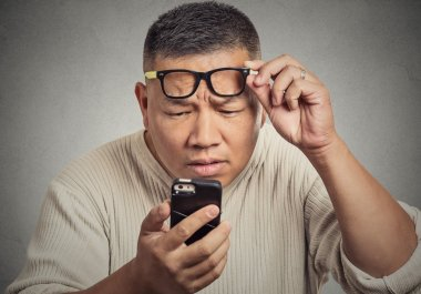 man with glasses having trouble seeing phone screen vision problems