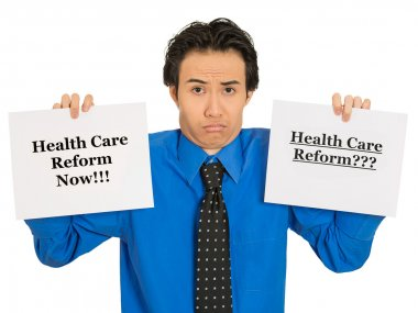 confused business man holding healthcare reform sign puzzled
