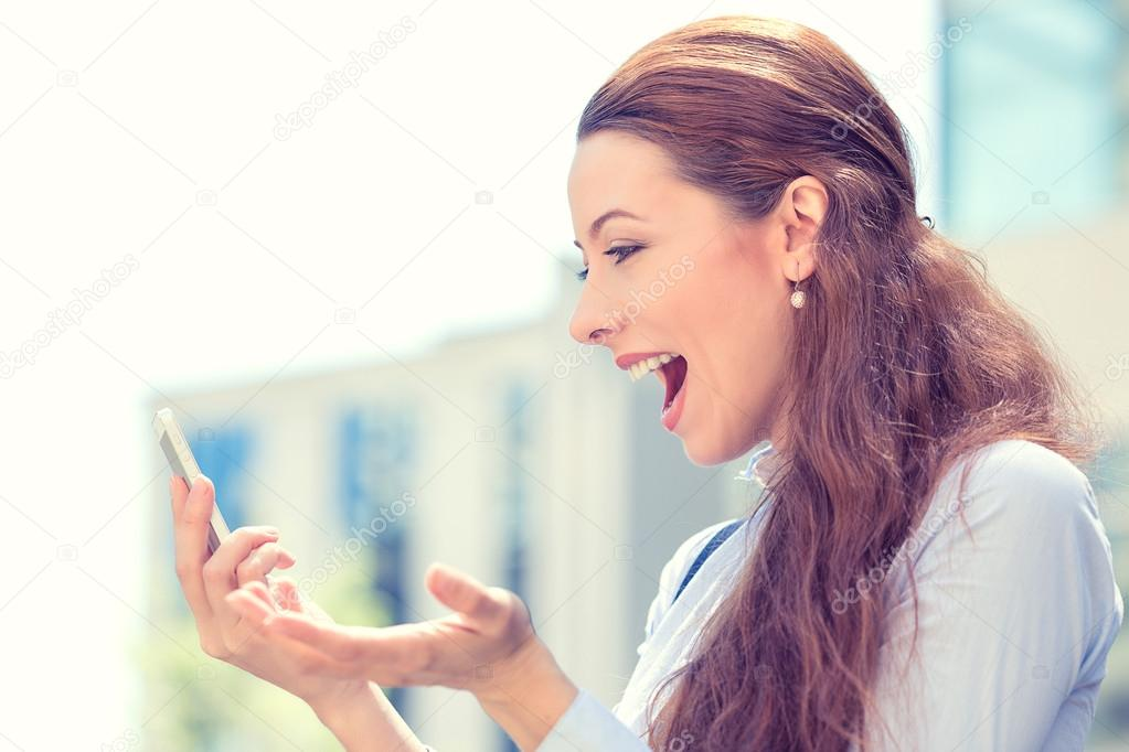 Surprised excited young girl looking at phone