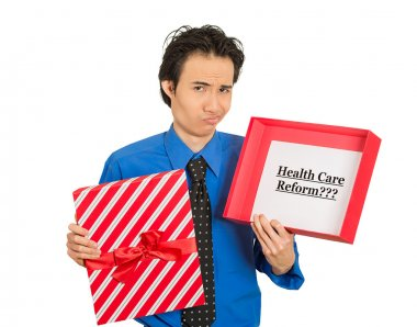 confused skeptical man holding sign health care reform in gift box
