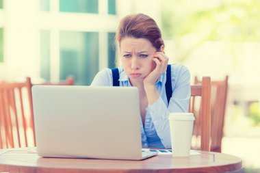 displeased worried business woman sitting in front of laptop computer