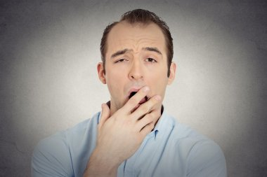 headshot sleepy young businessman funny guy placing hand on mouth yawning