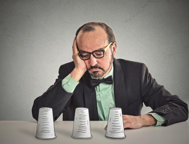 Man with glasses sitting at desk playing a conjuring trick game