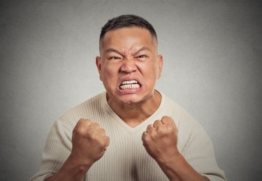 headshot angry man with open mouth fist up in air aggressive screaming