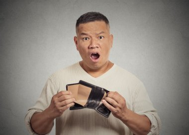 Shocked puzzled business man worker employee holding empty wallet