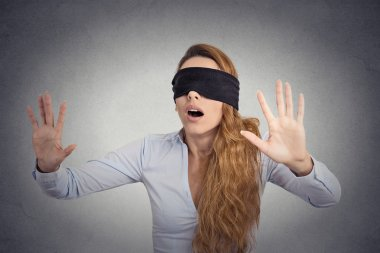 Young businesswoman walking blindfolded with hands forward