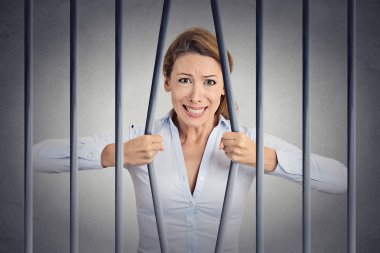 Stressed desperate angry businesswoman bending bars of her prison