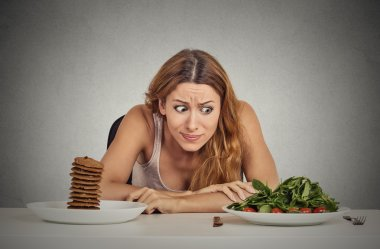 Woman deciding whether to eat healthy food or sweet cookies she craving