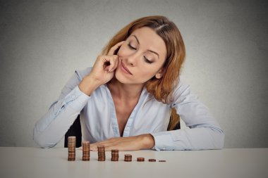 business woman corporate executive sitting at table with growing stack of coins