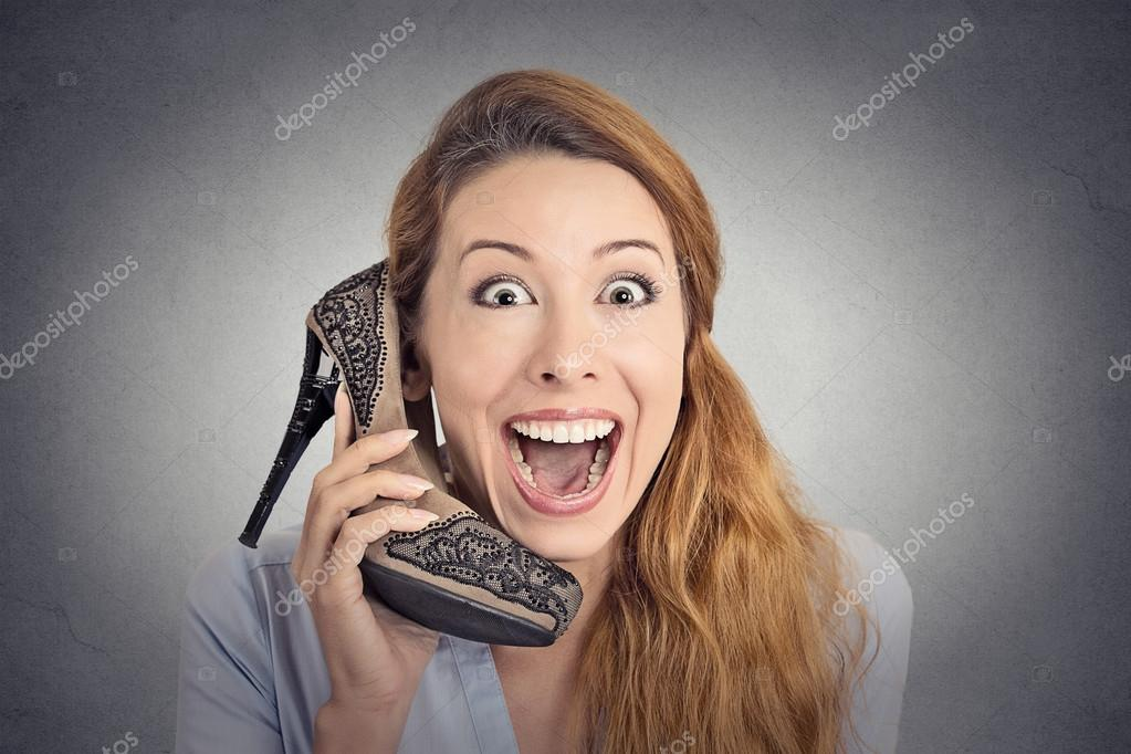 Headshot happy woman looking excited holding high heeled shoe as phone