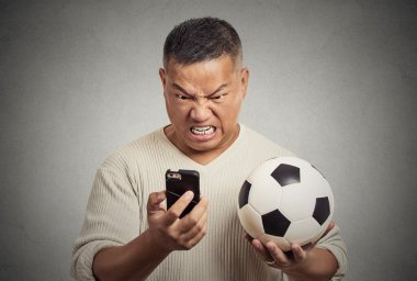 frustrated man looking on cell smart phone watching game holding football