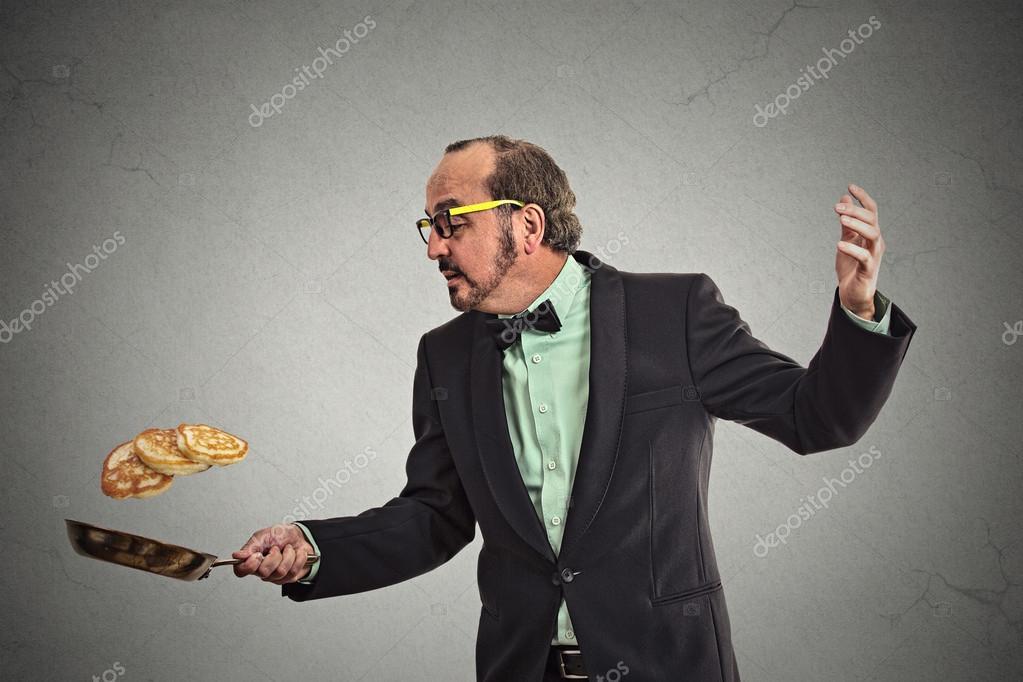 smiling man tossing pancakes on frying pan