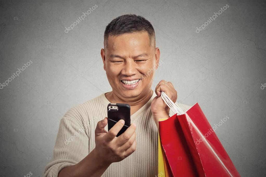 Smiling handsome man holding red shopping bags looking at his smartphone