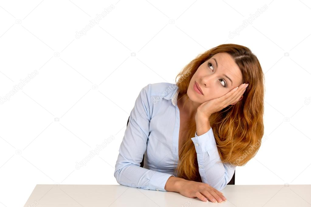 Bored woman leaning on a desk, thinking looking up