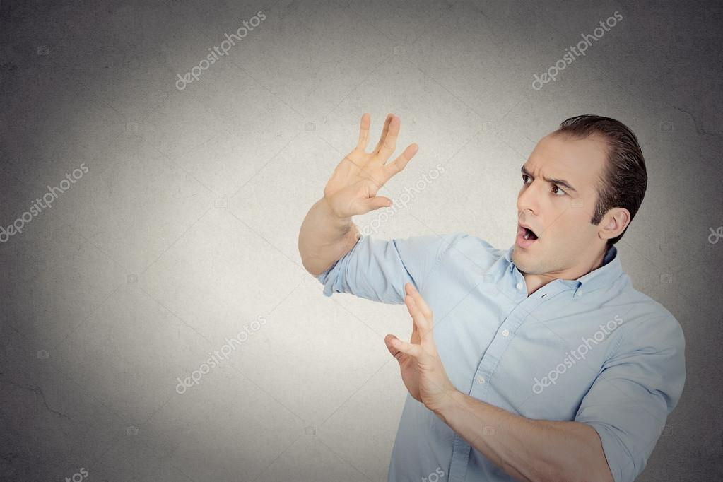 Man looking shocked scared trying to protect himself