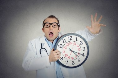 Busy, unhappy male health care professional, funny looking doctor holding wall clock