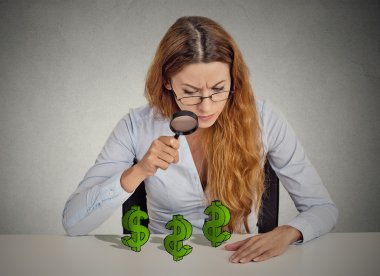 Business woman looking through magnifying glass at dollar signs