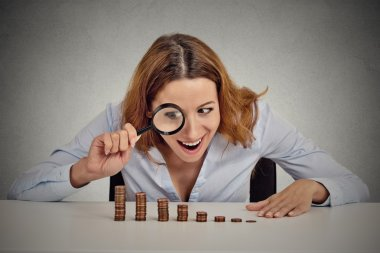 greedy business woman looking at stack of coins through magnifying glass