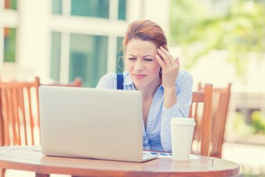 stressed displeased worried business woman sitting in front of laptop computer