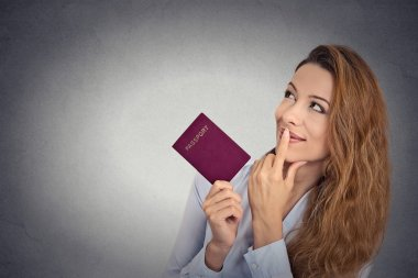 smiling happy woman standing holding passport looking up imagining new life