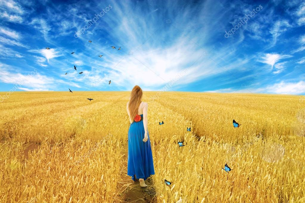 woman in dress standing walking through open wheat field