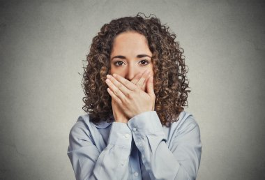 Woman covering closed mouth with hands. Speak no evil