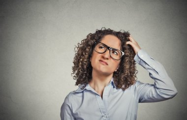 woman with glasses scratching head, thinking confused