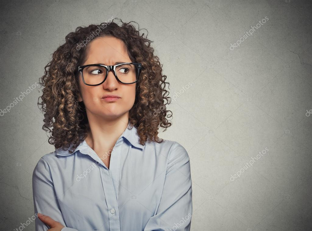 Displeased suspicious young woman with glasses