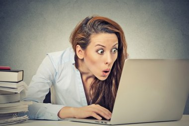 Shocked business woman sitting in front of laptop computer