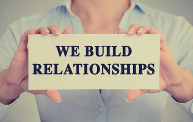 businesswoman hands holding card with we build relationships message