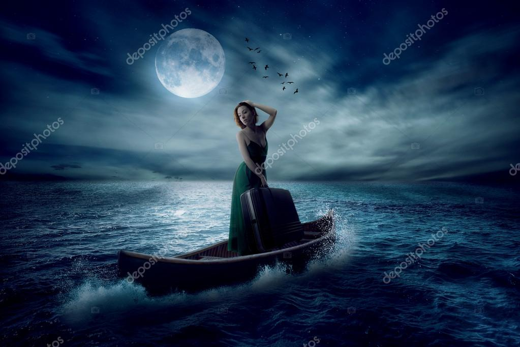 stylish woman with suitcase standing on a boat in a middle of the ocean