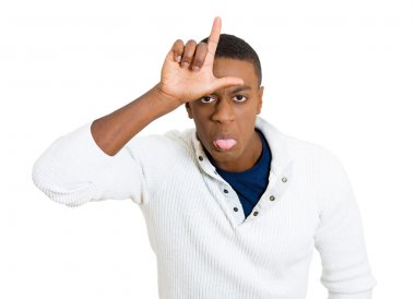 funny young man showing loser sign on his forehead