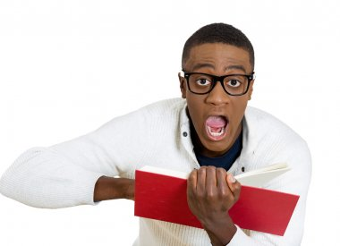 man wide opened eyes mouth pointing at a page inside book