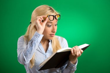 woman with glasses reading looking at book shocked surprised