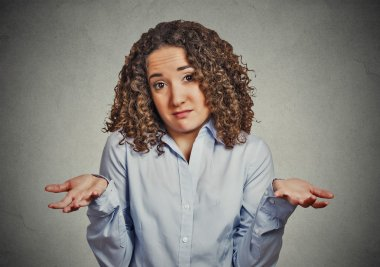 woman arms out shrugs shoulders in doubt