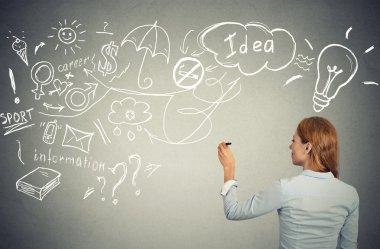 woman writing with pen many ideas on grey wall blackboard